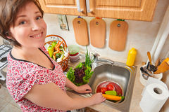 Woman wash vegetables and fresh greens in kitchen interior, healthy food concept Royalty Free Stock Images