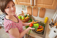 Woman wash vegetables and fresh greens in kitchen interior, healthy food concept Stock Photos