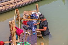 Woman washes clothes. INDEIN, MYANMAR - FEBRUARY 28, 2013: A woman washes clothes in the lake Stock Image