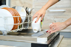 The woman washes the  dishes in the dishwashing machine. Stock Photos