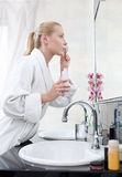 Woman washes face with lotion Stock Images