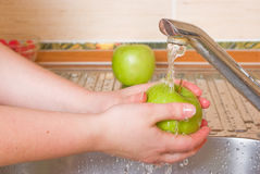 The woman washes a green apple Royalty Free Stock Photo