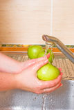 The woman washes a green apple Stock Photography