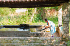 A woman washes her clothes in the wash house Stock Image