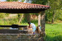 A woman washes her clothes in the wash house Royalty Free Stock Photo