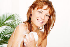 Woman washes herself with a sponge Stock Photography