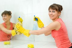 The woman washes a mirror. In a bathroom stock photo