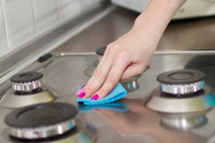 Woman washes a stove Royalty Free Stock Image