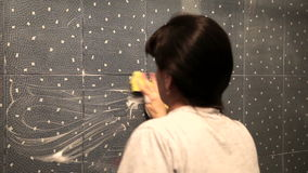 Woman washes the tile on the wall with a cloth lather stock footage