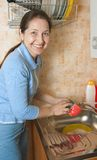 Woman washes ware. Woman washing dirty dishes in the kitchen sink Royalty Free Stock Photo