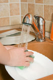 The woman washes ware on kitchen Stock Photo