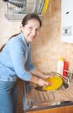 Woman washes ware on kitchen. Senior woman is washing the dishes in the kitchen Royalty Free Stock Photography