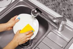 Woman that washes a white dish Royalty Free Stock Photos