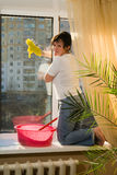 A woman washes a window. In a house Royalty Free Stock Image
