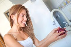 Woman washing an apple Royalty Free Stock Photos