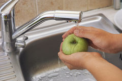 Woman washing an apple with water in sink Stock Photography
