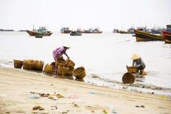 Woman washing baskets on fish sauce production, Mui Ne, Vietnam Royalty Free Stock Photos