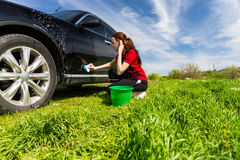 Woman Washing Black Car with Sponge in Green Field Stock Photo