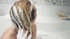 Woman with shampoo on hair, in bath stock footage