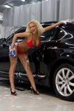 Woman washing a car. A woman washing a car in a bikini Royalty Free Stock Photography