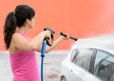 Woman washing car. Woman cleaning silver car with water jet Royalty Free Stock Images