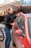 Woman washing car roof with rag Royalty Free Stock Photos