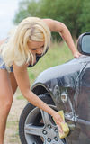 Woman washing car with sponge. Royalty Free Stock Photos