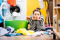 Woman washing clothes at home. Tired housewife lying on the floor with lots of clothes near the washing machine at home Stock Photo