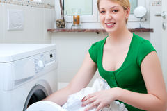 Woman washing clothes with machine Stock Images