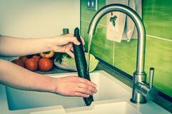 Woman washing cucumber for salad - retro style Stock Photos