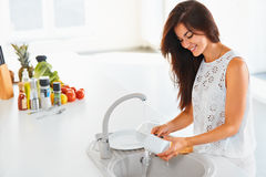Woman washing a cup in white kitchen. Vegetables on the backgrou Royalty Free Stock Photography