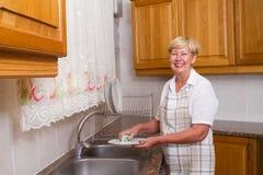 Woman washing dishes Royalty Free Stock Photos