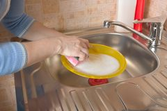 Woman washing dishes in her kitchen Royalty Free Stock Photos