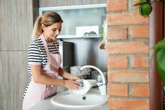 Woman washing dishes in kitchen sink. Cleaning chores stock image