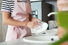 Woman washing dishes in kitchen sink, closeup view. stock image