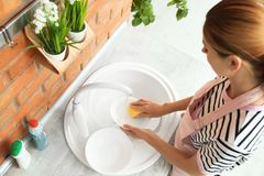 Woman washing dishes in kitchen sink. Cleaning chores royalty free stock images