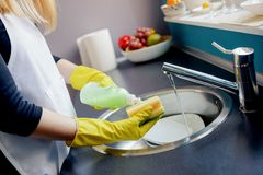 Woman washing dishes in the kitchen with sponge. Royalty Free Stock Photography