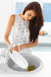 Woman washing the dishes in modern  kitchen. Royalty Free Stock Images