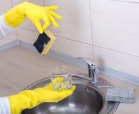 Woman washing dishes wih dirty sponge Royalty Free Stock Image