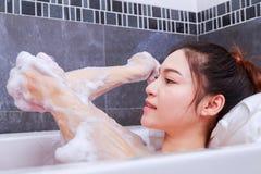 Woman washing elbow with sponge in bathtub in the bathroom. Woman washing elbow with pink sponge in bathtub in the bathroom Royalty Free Stock Photography