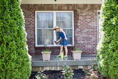Woman washing the exterior windows of a house Royalty Free Stock Photography