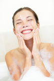 Woman washing face in bath. Face wash. Woman washing face in bath with foam. Young Asian / Caucasian woman cleaning her face in bathtub smiling happy Royalty Free Stock Photo
