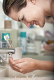 Woman Washing Face In Bathroom Royalty Free Stock Image