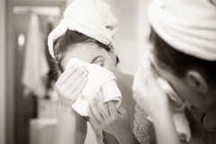 Woman washing face in bathroom. Hygiene. Woman cleaning washing her face with clean water in bathroom. Girl taking care of her complexion. Morning hygiene Royalty Free Stock Photo
