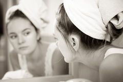 Woman washing face in bathroom. Hygiene. Woman cleaning washing her face with clean water in bathroom. Girl taking care of her complexion. Morning hygiene Stock Photo