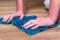 Woman washing floor with blue rag. royalty free stock image