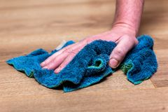 Woman washing floor with blue rag. stock photography