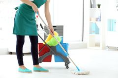 Woman washing floor in office. Cleaning service concept stock photos