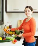 Woman washing fresh vegetables in sink Stock Images