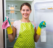 Woman washing fridge at home Stock Photo
